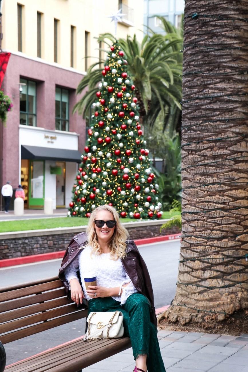 Burgundy leather moto jacket paired with a girly white blouse, lace pants and velvet heels. #holidaystyle #holidayoutfitinspo #holidayparty #holidayseason
