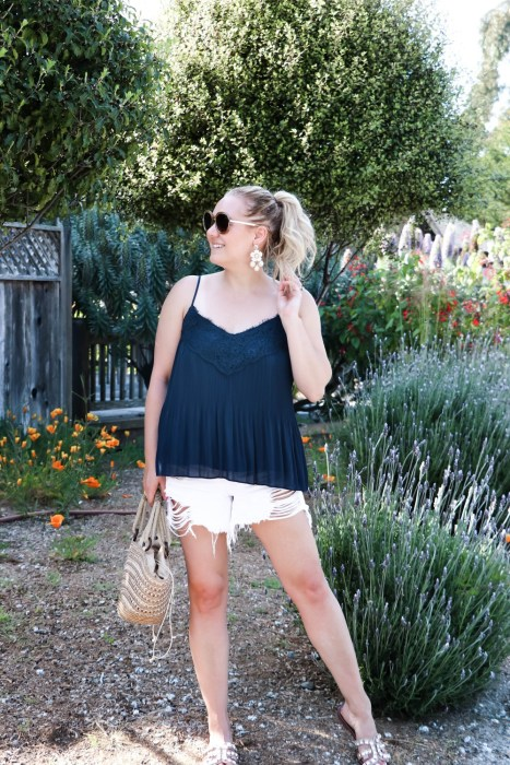 The perfect Summer mom uniform is a swing cami and distressed white denim shorts. I have been living in these 3x1 Blake shorts and I plan to all Summer long! Head on over to the blog to check out the full post + get my outfit details and find out where you can shop this look! #summerstyle #summeruniform #momuniform #momstyle #stylishmoms
