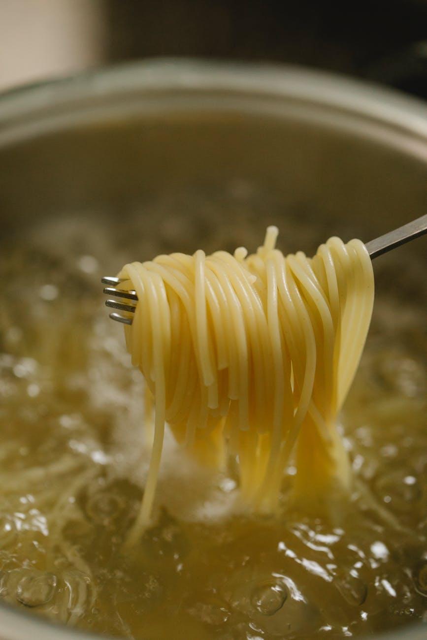 spaghetti spun on fork above boiling water in saucepan