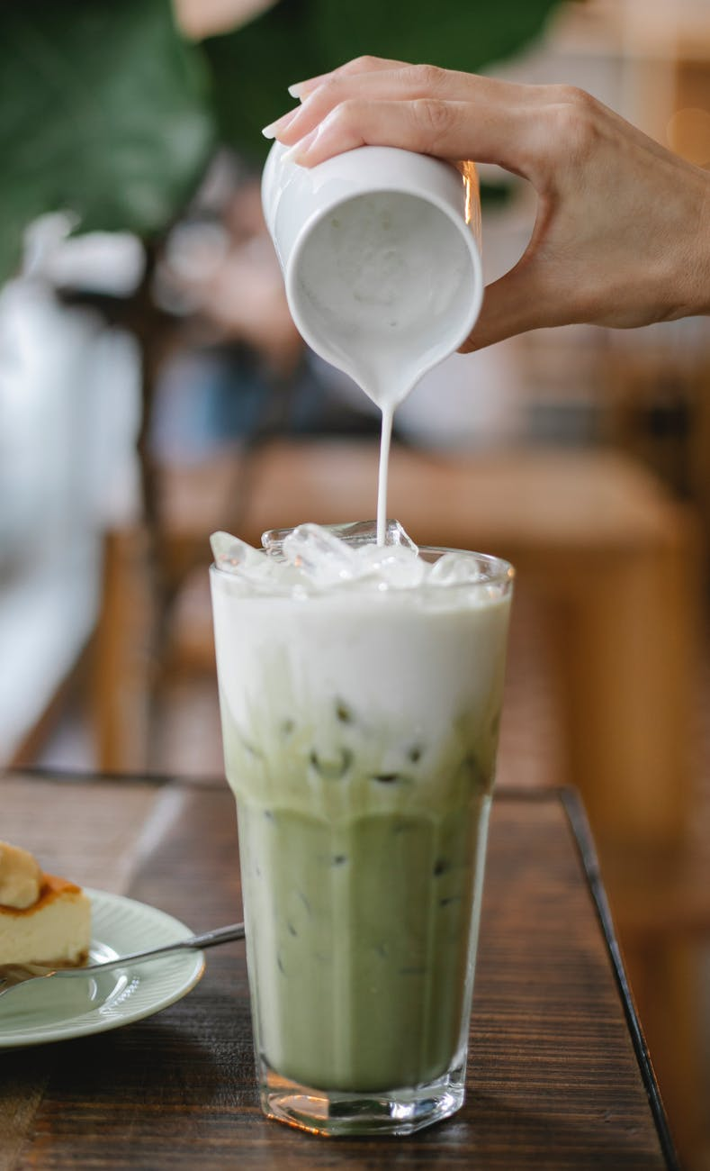 crop faceless woman pouring milk into glass of matcha latte
