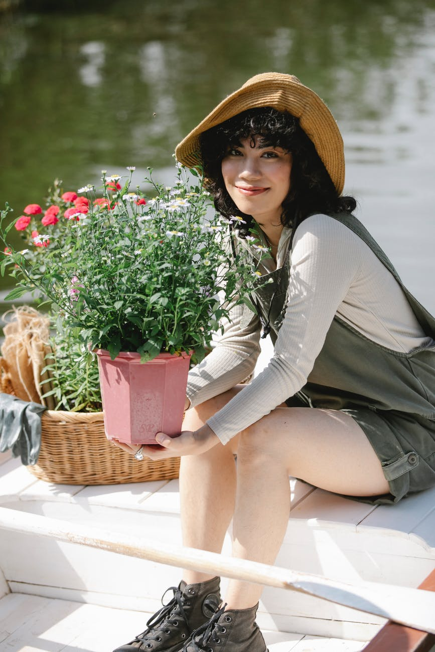 ethnic female gardener in boat with potted flowers in river