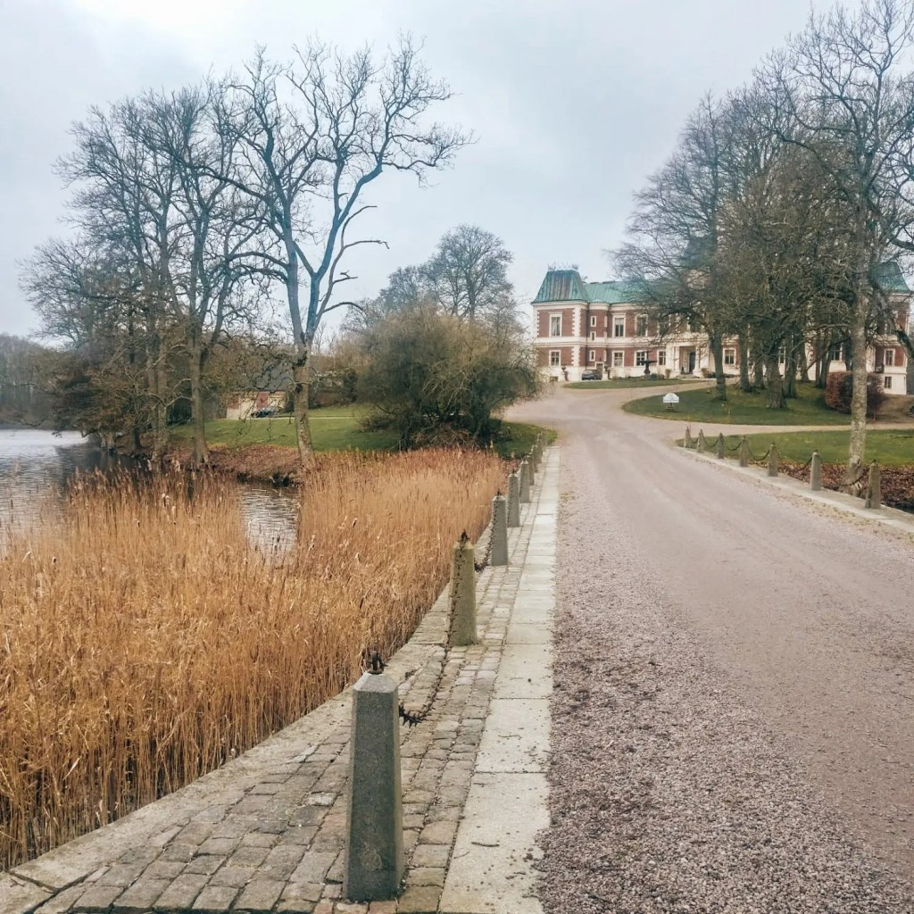 A long drive way with water on either side, leads out to a peninsula with a old castle style manor from the 1800s on it.