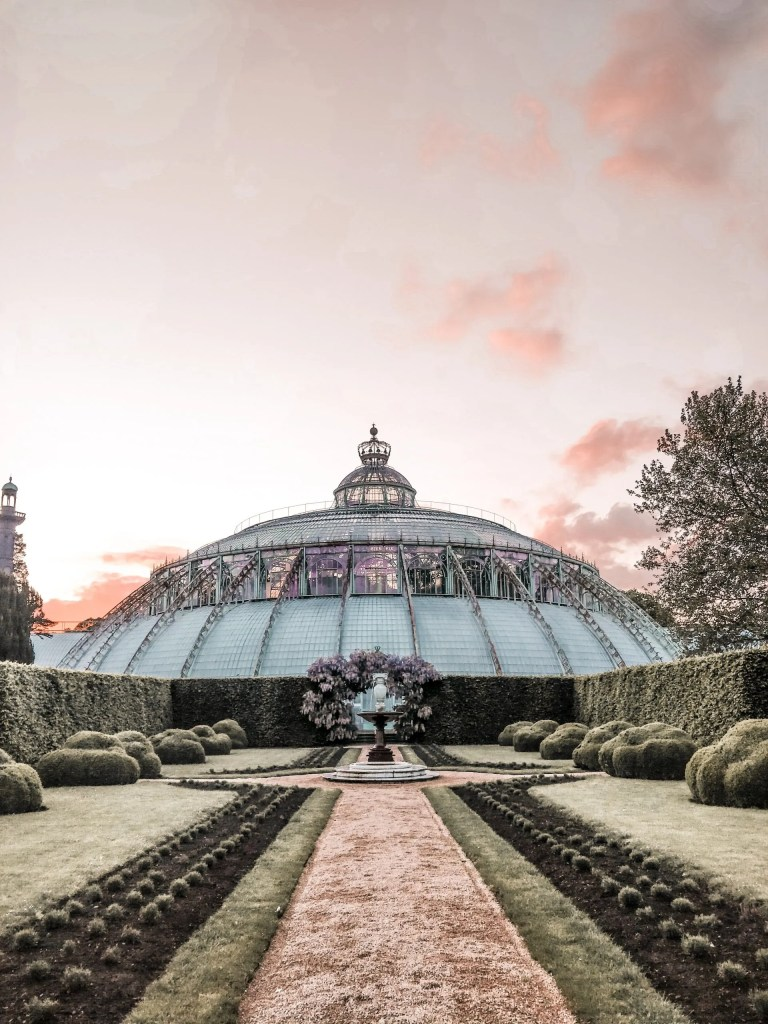 The glass dome of the royal greenhouses of laeken in Brussels at sunset.