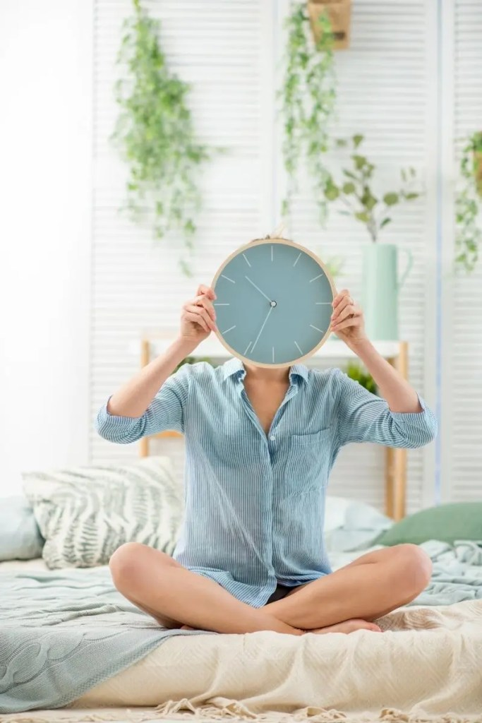 woman holding clock in front of her face