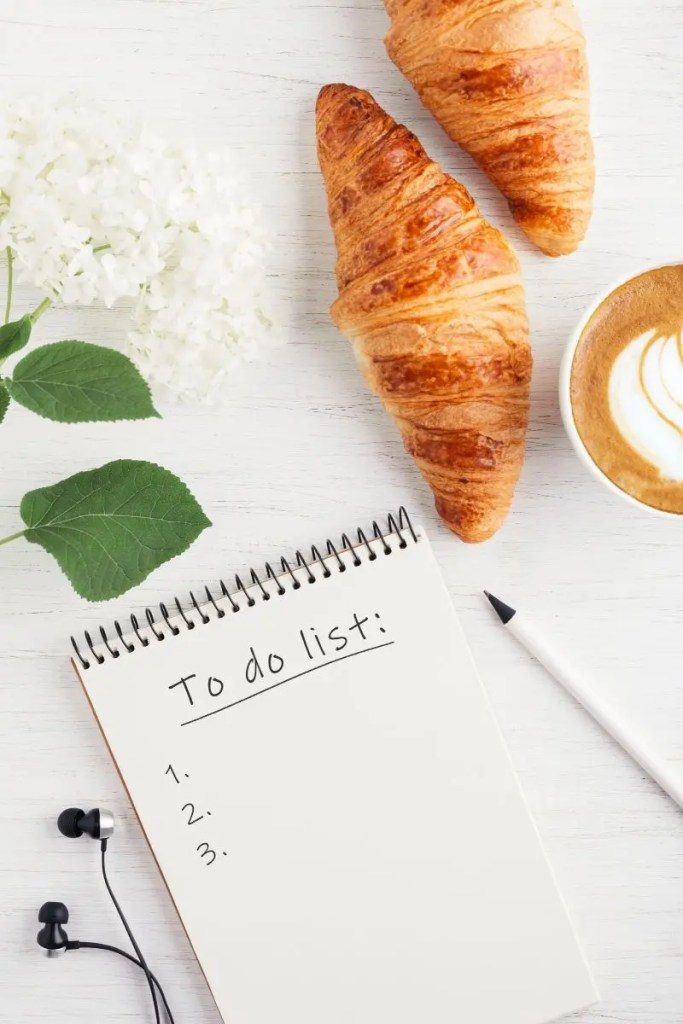 notebook with to do list and croissants, coffee and flowers
