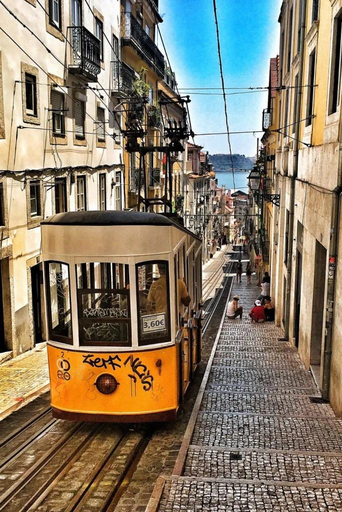 Yellow streetcar driving on a narrow street