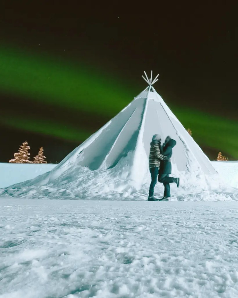 A couple kissing under the Northern Lights over the ice hotel in sweden.