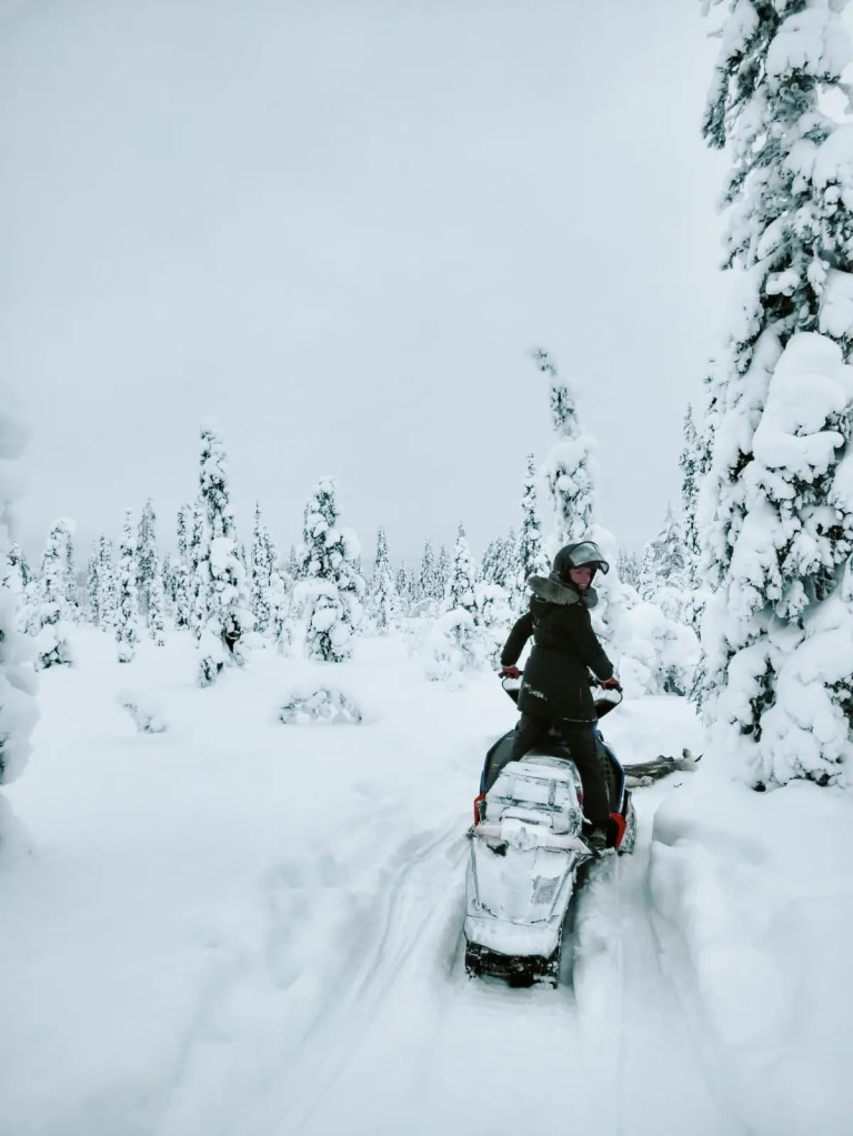 A woman driving a snow mobile during a Sweden winter holiday.