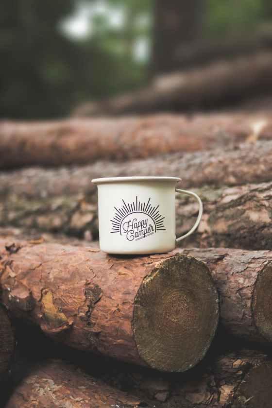 white happy camper printed cup on brown wooden log