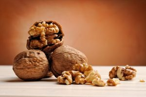 group of walnuts on a white wooden table with brown background
