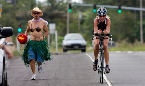 Johnny Phillips, left, jogs next to triathlete Shanna Armstrong along the Keaau Bypass (Hwy 130)  heading towards Hilo during the second day of the Ultraman Triathlon. Phillips is part of Armstrong's support team during the three day event which started and finishes in Kailua-Kona