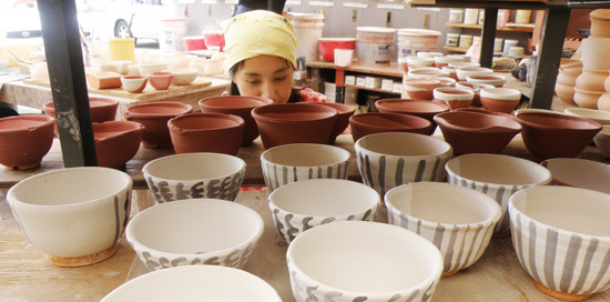 Director of DMAC's ceramic department Tomoko Nakazato drowning in a sea of bowls. (Photo courtesy of Donkey Mill Art Center)