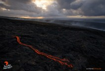 The sun rises over the Kalapana coast, as a river of lava continues the slow advance of the March 5th breakout.