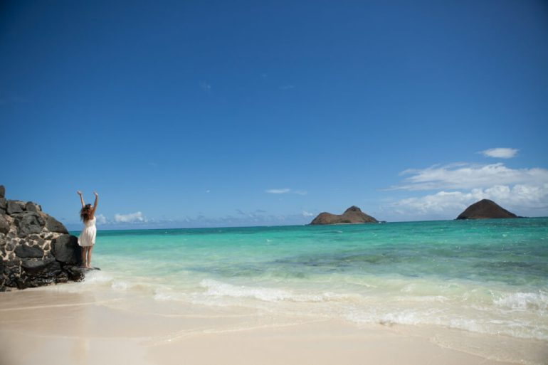 Lanikai Beach is one of the best beaches on Oahu for families. Image of a woman with her arms stretched up standing on the beach overlooking two little islands.