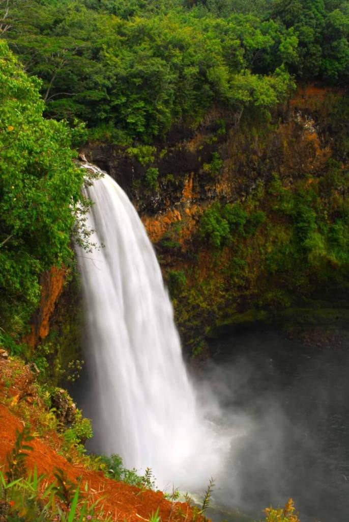 Wailua Falls is one of the most popular waterfalls on Kauai. Image of a gushing waterfall surrounded by greenery and red dirt.