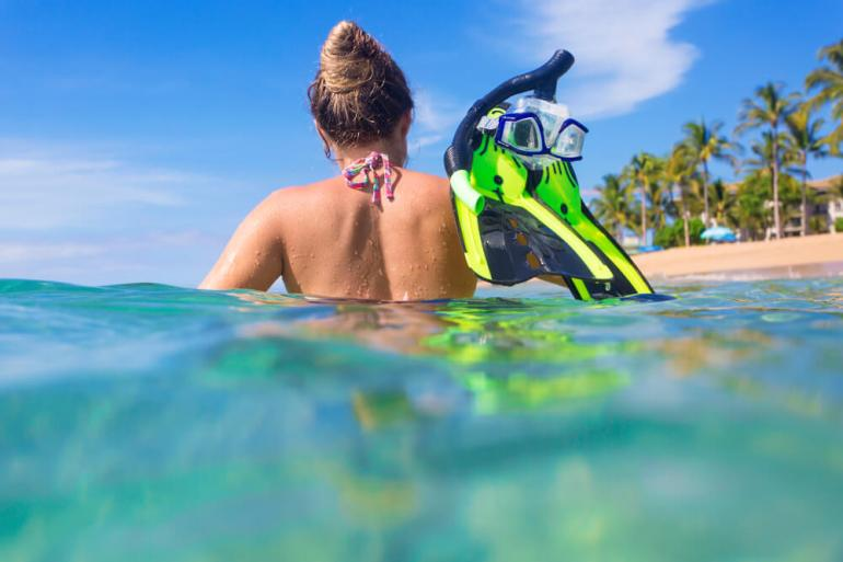 It's worth buying snorkel gear in Hawaii if you do it more than once. Image of a woman in the ocean holding snorkel gear in her hand.