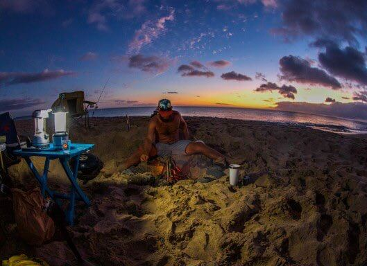 Guide to Camping in Hawaii featured by top Hawaii blog, Hawaii Travel with Kids. | You'll want to bring your own cooking equipment like this grill and cooler in the photo of a man camping in Hawaii