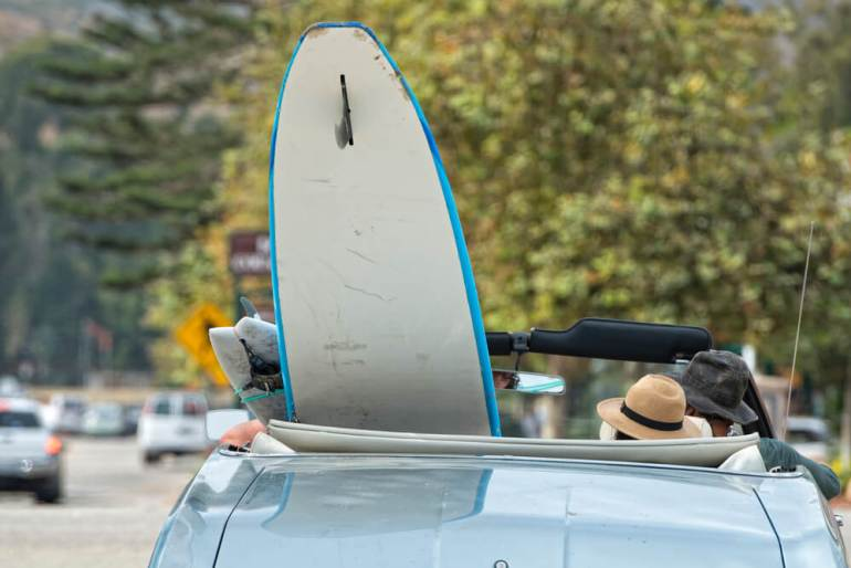 Find out how to rent a car in Hawaii by top Hawaii blog Hawaii Travel wth Kids. Image of a surfboard in a convertible.
