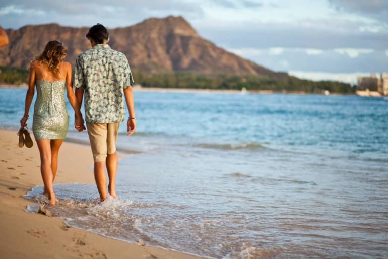Visiting Hawaii in February with your Family, a travel guide featured by top Hawaii blog, Hawaii Travel with Kids: image of Couple walk along Waikiki with Leahi in back, Oahu