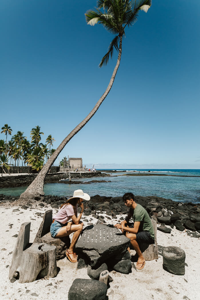 Where to Stay on the Big Island: Kona or Hilo, tips featured by top Hawaii blog, Hawaii Travel with Kids: Visitors play konane, a checkers-like game, at Puuhonua o Honaunau