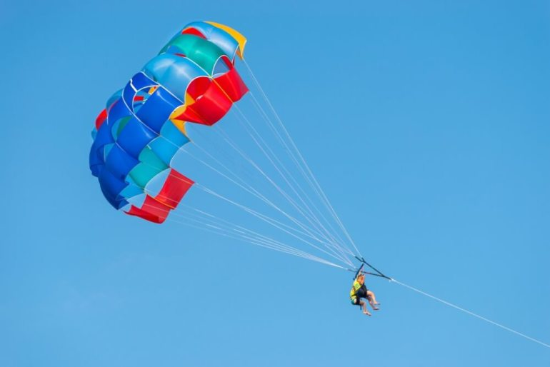 6 Best Places to Go Parasailing on Maui featured by top Hawaii blog, Hawaii Travel with Kids: Man parasailing in Hawaii