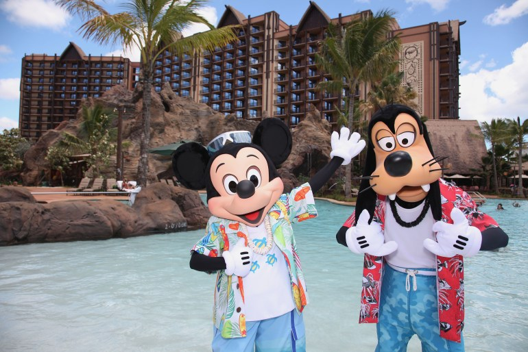 One of the Best Oahu Resorts for Families who love Disney is Aulani Resort. Image of Mickey and Goofy wearing Aloha shirts in front of the pool at Aulani Resort on Oahu.