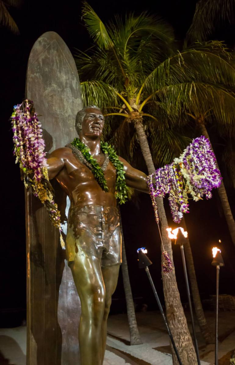 50 Best Places to Visit in Hawaii with your Family featured by top Hawaii blog, Hawaii Travel with Kids: Duke Kahanamoku statue at night.