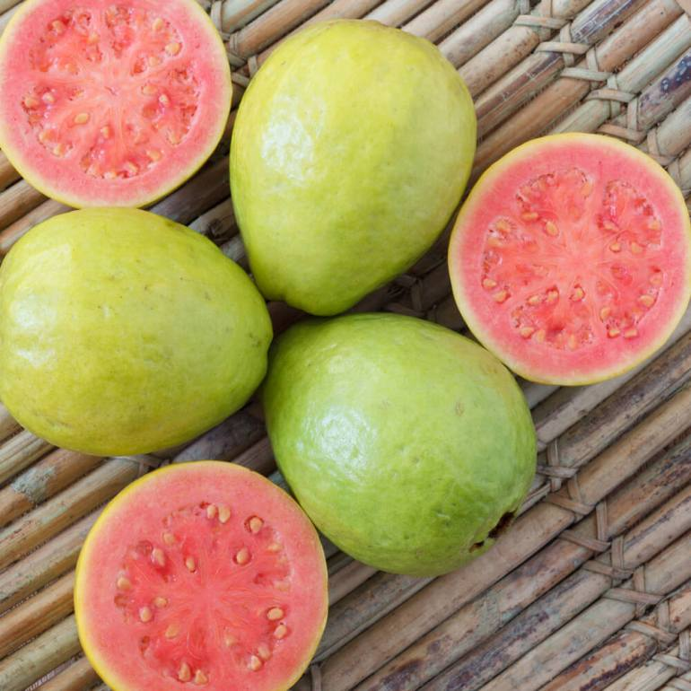 15 Hawaiian Fruits to Try featured by top Hawaii blog, Hawaii Travel with Kids: Fresh guava on a wooden table