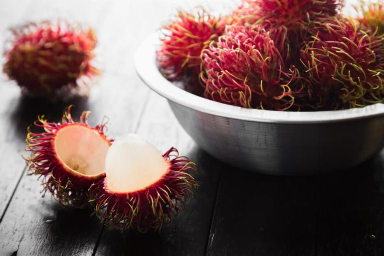 15 Hawaiian Fruits to Try featured by top Hawaii blog, Hawaii Travel with Kids: Fresh rambutan on wooden table background