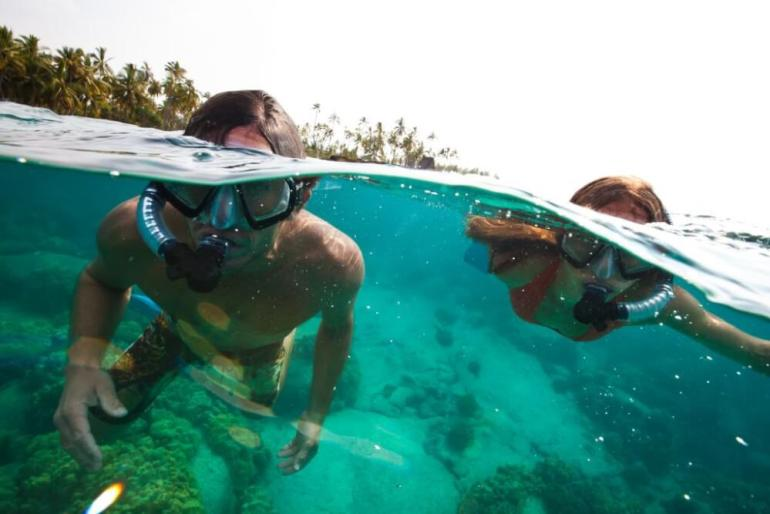 Find out where to snorkel on Maui with kids. Image of kids snorkeling on Maui.