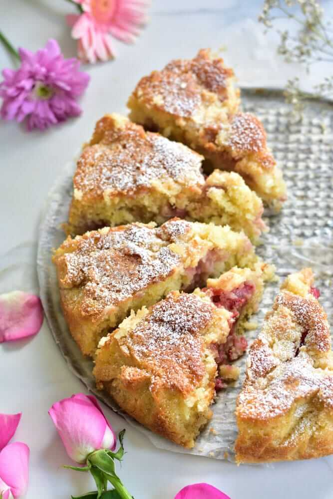61 Delicious Coconut Dessert Recipes Perfect for Summer featured by top Hawaii blog, Hawaii Travel with Kids: Strawberry coconut cake cut into servings, flowers scattered around