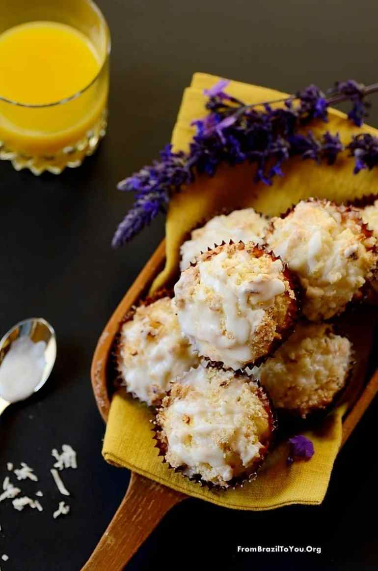 61 Delicious Coconut Dessert Recipes Perfect for Summer featured by top Hawaii blog, Hawaii Travel with Kids: Serving Mango Coconut Streusel Muffins in a platter with flowers on the side and a glass of juice