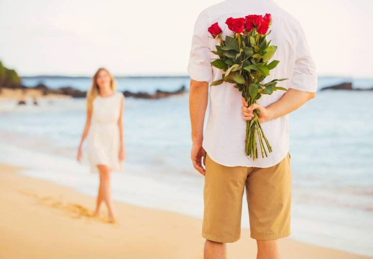Top 10 Romantic Hawaii Beach Proposal Ideas + Locations featured by top Hawaii blog, Hawaii Travel with Kids: Young Couple in Love, Man holding surprise bouquet of roses for beautiful young woman, Romantic Date