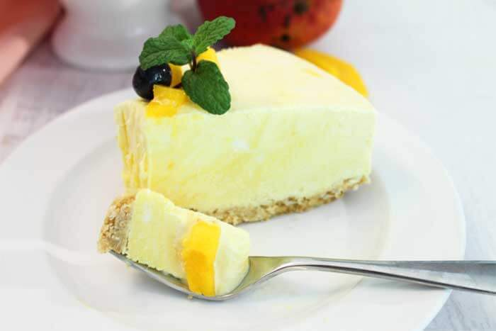 Best Mango dessert recipes by top Hawaii blog Hawaii Travel with Kids: Mango Pineapple Icebox Cheesecake slice with bite