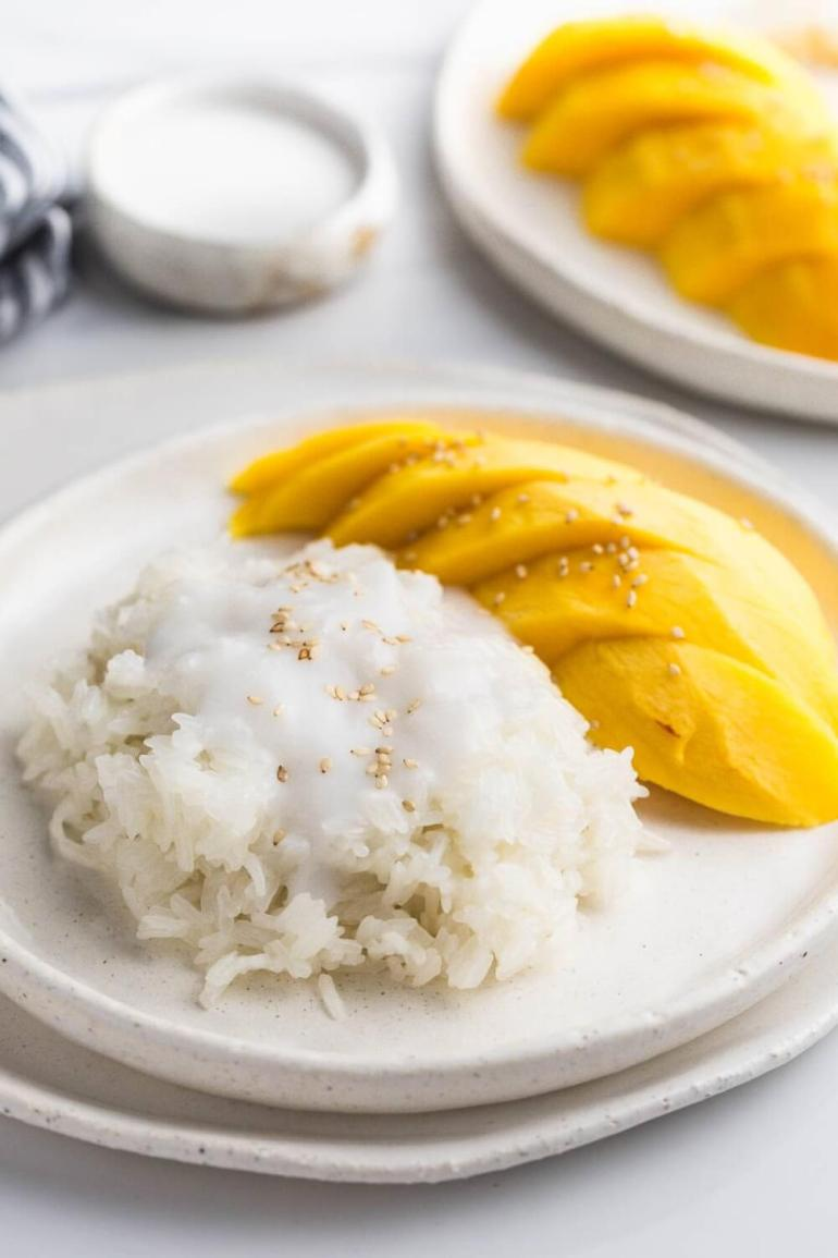 Best Mango dessert recipes by top Hawaii blog Hawaii Travel with Kids: Mango sticky rice, with fresh mango on the side on a white plate. On a white ceramic tray