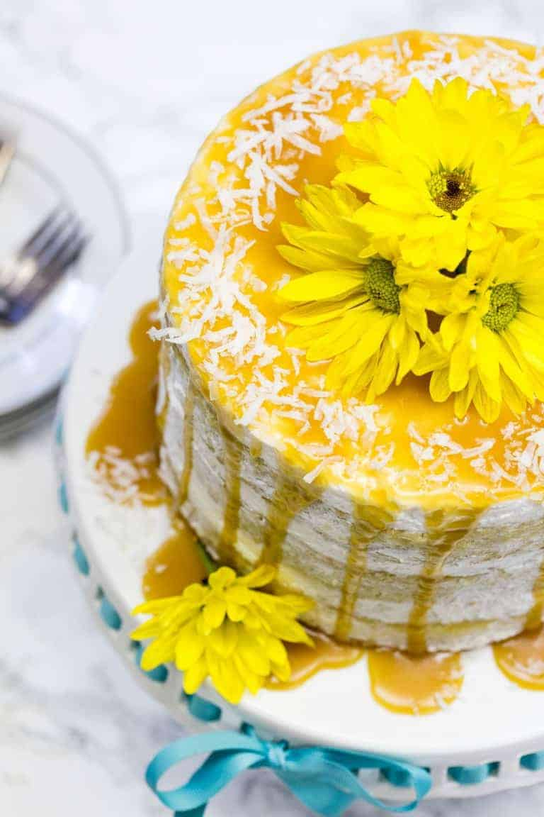 Best Mango dessert recipes by top Hawaii blog Hawaii Travel with Kids: overhead view of mango cake on a cake pan with yellow flowers on top