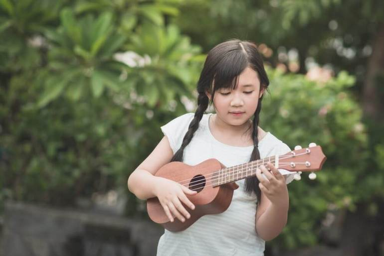 Learn how to choose the best kids ukulele by top Hawaii blog Hawaii Travel with Kids. Image of a girl playing a kids ukulele