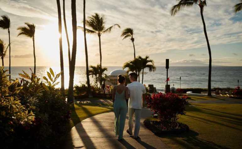 Top 5 Best Maui Luxury Hotels featured by top Hawaii blogger, Hawaii Travel with Kids: The Fairmont Kea Lani is one of the best Maui luxury hotels. Image of a couple walking at this Maui hotel at sunset