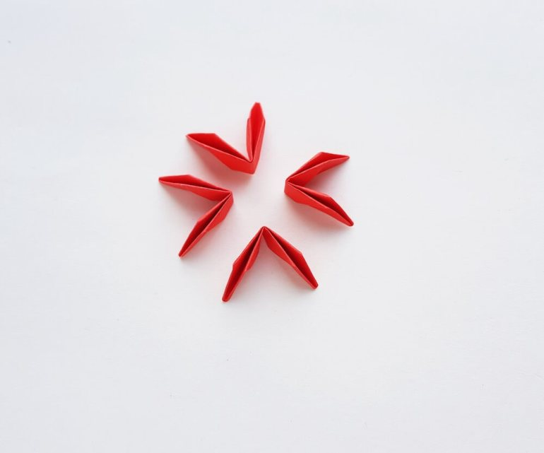 How to Make Origami Poinsettia Flowers, a Hawaiian Christmas craft tutorial featured by top Hawaii blogger, Hawaii Travel with Kids: Image of 4 folded pieces of red paper