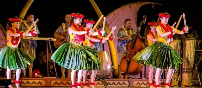 The Ka Wa'a luau is one of the best luaus on Oahu for families. Image of several female hula dancers wearing ti leaf skirts and playing with split bamboo.