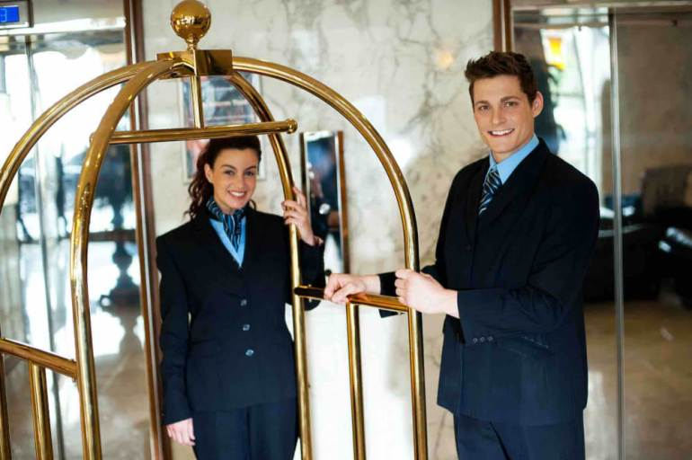 Tipping in Hawaii can be tricky. Find out how much to tip the bellhop in Hawaii. Image of two bellhops with a luggage cart.