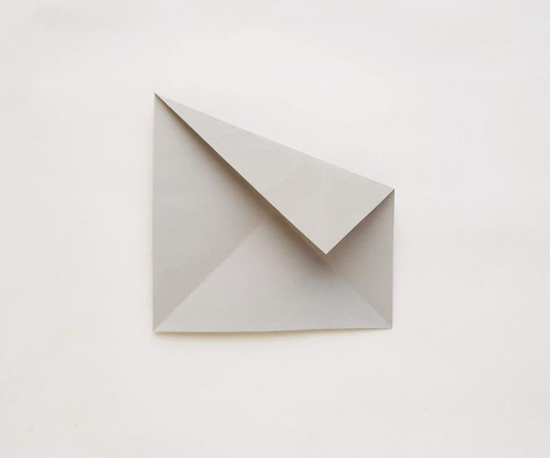 Find out how to make an origami shark for kids. Image of a grey piece of paper folded.