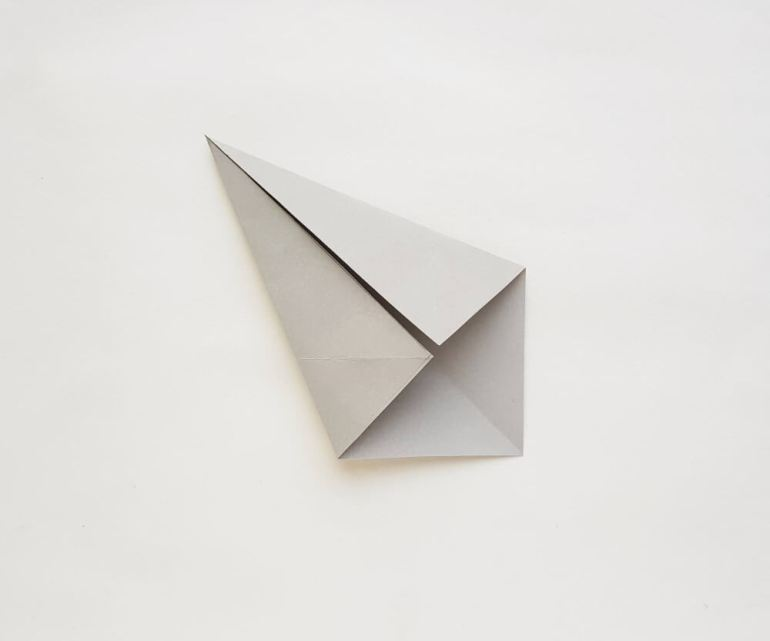 Get my origami shark tutorial. Image of a grey piece of paper folded.