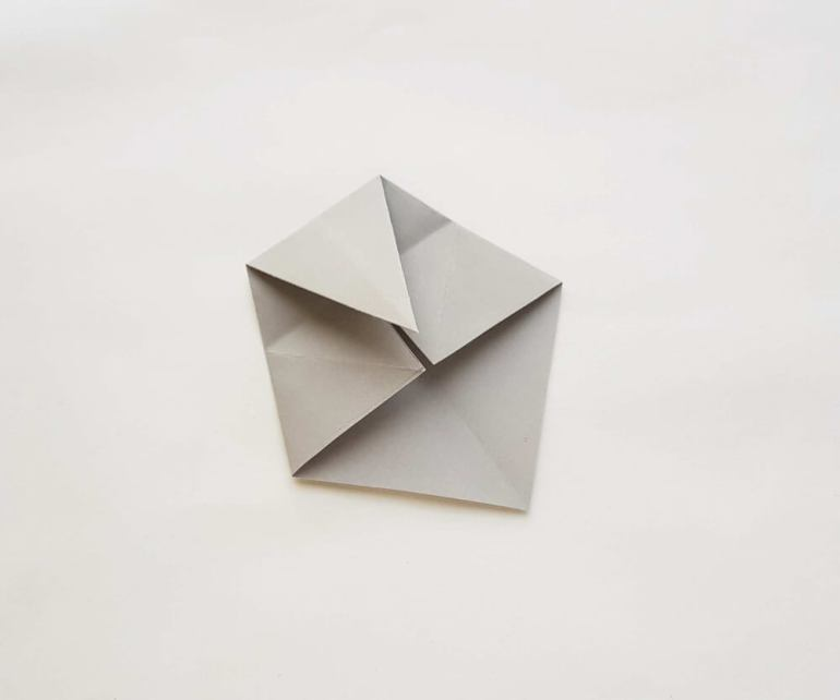 Learn how to make a origami shark. Image of a piece of grey paper folded.