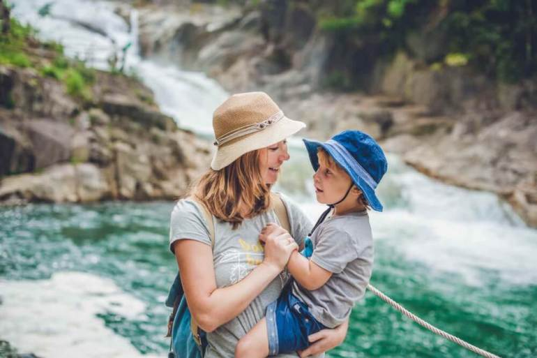 Find out the best things to do in Hawaii with toddlers by top Hawaii blog Hawaii Travel with Kids. Image of Mother and son relaxing under a waterfall. Vacation concept.