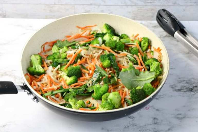 Stir fry the vegetables in a pan. Image of chopped broccoli, carrots, and bean sprouts in a skillet.