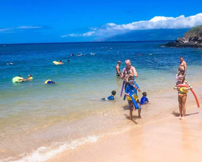 Find out all the best snorkeling Hawaii has to offer. Image of a family wearing snorkel gear and pool noodles.