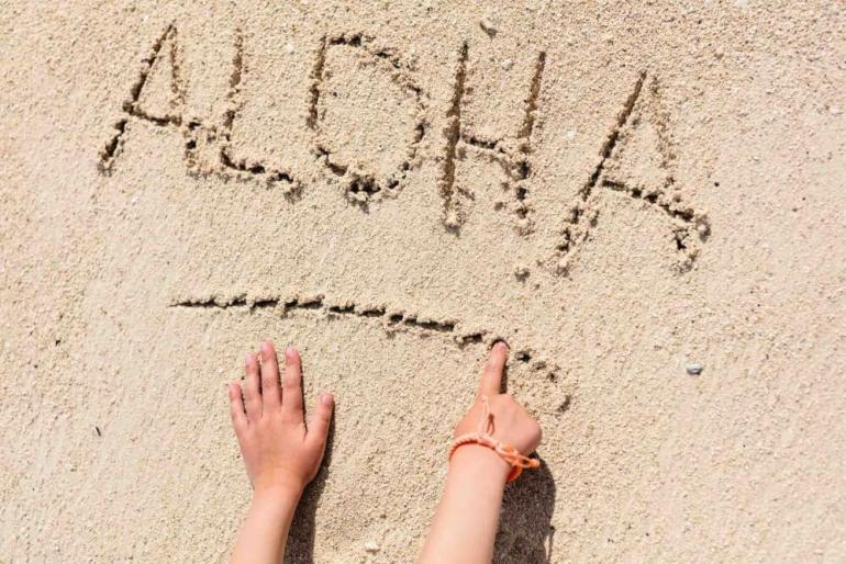 One of the fun facts about Hawaii is that there are no private beaches. Image of the word Aloha written in the sand.