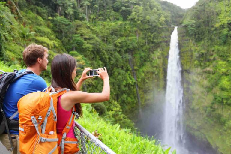 Find out the best things to do on the Big Island by top Hawaii blog Hawaii Travel with Kids.Image of a couple of tourists on Hawaii by waterfall.