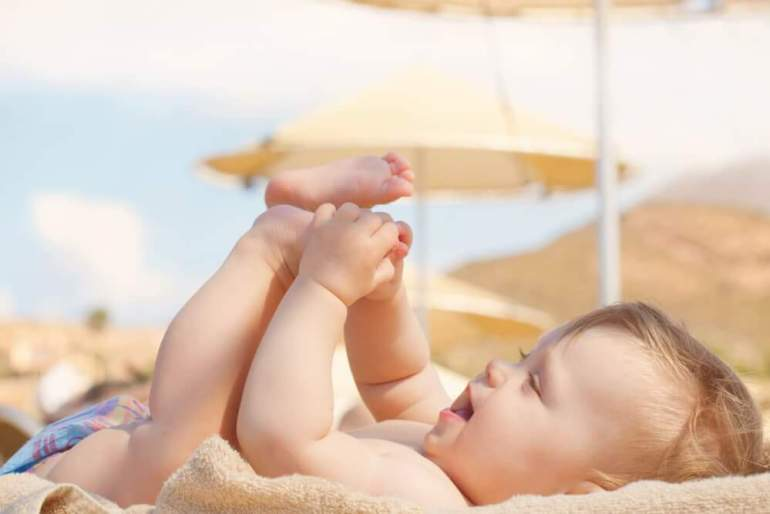 Where should you stay in Hawaii with a baby? Image of Happy baby on the beach. 8 month old kid lying on a sun lounger and playing with her feet.